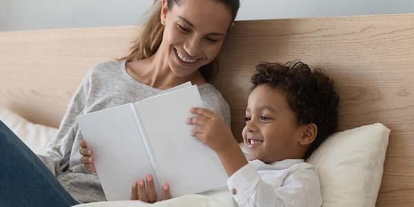 Hispanic mother and son reading in bed